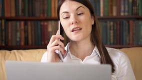 Mujer ocupada que se sienta en casa con el ordenador portátil y el smartphone Discusión de proyecto sobre la pantalla por el telé almacen de video