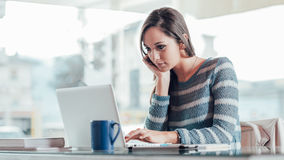Mujer ocupada que trabaja con su ordenador portátil Imagenes de archivo