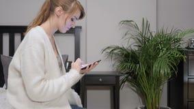 Mujer ocupada usando el teléfono para Internet que hojea almacen de metraje de vídeo