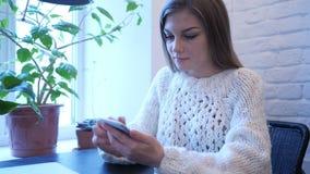 Mujer ocupada usando el teléfono para Internet que hojea almacen de video