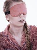 Mujer so?olienta que lleva la banda rosada del ojo fotos de archivo libres de regalías