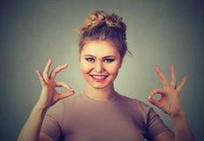 Mujer optimista joven feliz emocionada que da gesto aceptable de la muestra con dos manos fotografía de archivo libre de regalías