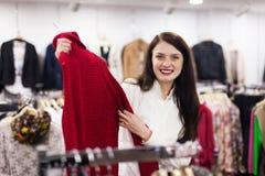 Mujer ordinaria que elige el suéter Fotos de archivo