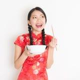 Mujer oriental en qipao rojo que come con los palillos Imagen de archivo libre de regalías