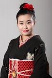 Mujer oriental hermosa en kimono japonés negro Foto de archivo