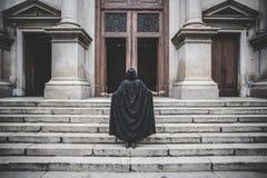 Mujer oscura hermosa del vampiro con la capa y la capilla negras Imagen de archivo libre de regalías
