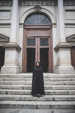 Mujer oscura hermosa del vampiro con la capa y la capilla negras Fotografía de archivo libre de regalías