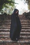 Mujer oscura hermosa del vampiro con la capa y la capilla negras Fotos de archivo libres de regalías