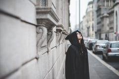Mujer oscura hermosa del vampiro con la capa y la capilla negras Imágenes de archivo libres de regalías