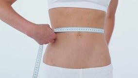 Mujer pacífica que mide su cintura