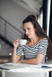 Mujer pacífica que se relaja en un café con una taza de té Café de consumición femenino sonriente casual feliz y mirada Foto de archivo