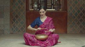 Mujer pacificada que juega glucophone con los tambores