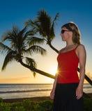 Mujer, palmeras y puesta del sol Fotos de archivo