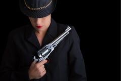 Mujer peligrosa en negro con la arma de mano de plata Fotos de archivo