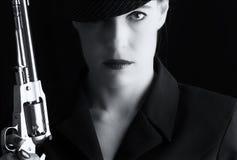 Mujer peligrosa en negro con la arma de mano de plata Foto de archivo