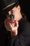 Mujer peligrosa en negro con la arma de mano de plata Imagen de archivo