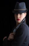 Mujer peligrosa en negro con la arma de mano de plata Imagen de archivo libre de regalías