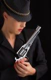 Mujer peligrosa en negro con la arma de mano de plata Fotos de archivo libres de regalías