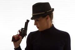 Mujer peligrosa en negro con la arma de mano grande Imagenes de archivo