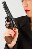 Mujer peligrosa en negro con la arma de mano grande Imagen de archivo libre de regalías