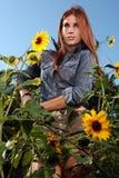 Mujer pelirroja al aire libre en un campo del girasol fotografía de archivo