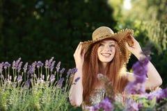 Mujer pelirroja atractiva con el sombrero de paja en verano fotografía de archivo libre de regalías