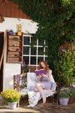 Mujer pelirroja atractiva que se relaja en jardín fotografía de archivo