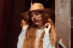 Mujer pelirroja bastante joven en sombrero de paja con la sombra en su fa Fotos de archivo libres de regalías