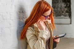 Mujer pelirroja con el dispositivo móvil cerca de la pared Imagen de archivo libre de regalías