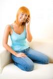 Mujer pelirroja con el teléfono celular Foto de archivo