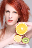 Mujer pelirroja con la naranja, el limón y el kiwi Foto de archivo libre de regalías