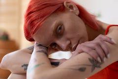 Mujer pelirroja con los tatuajes que sienten dolor y miseria imagen de archivo