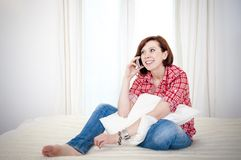 Mujer pelirroja en el sofá que habla en la célula móvil Imagen de archivo