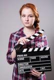 Mujer pelirroja hermosa que sostiene una chapaleta de la película Foto de archivo