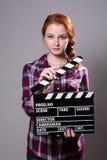 Mujer pelirroja hermosa que sostiene una chapaleta de la película Fotografía de archivo libre de regalías
