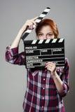 Mujer pelirroja hermosa que sostiene una chapaleta de la película, aislada sobre fondo gris Imagen de archivo
