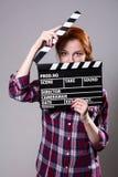 Mujer pelirroja hermosa que sostiene una chapaleta de la película, ove aislado Fotos de archivo libres de regalías