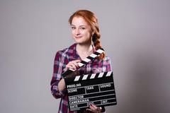 Mujer pelirroja hermosa que sostiene una chapaleta de la película, ove aislado Fotografía de archivo