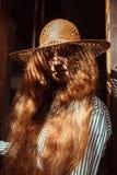 Mujer pelirroja joven preciosa en sombrero de paja con la sombra en su fa Imagen de archivo libre de regalías