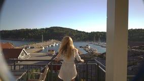 Mujer pelirroja joven que admira las opiniones del mar en la terraza del hotel en la costa en Europa del Norte almacen de metraje de vídeo