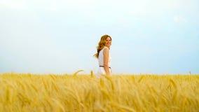 Mujer pelirroja juguetona joven que sonríe en la cámara y que oculta en campo de trigo metrajes
