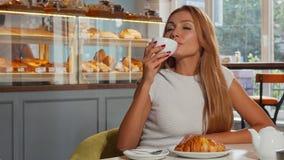 Mujer pelirroja preciosa que goza del café y del cruasán por la mañana almacen de video