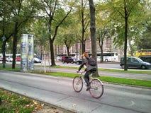 Mujer pelirroja que monta una bicicleta Foto de archivo libre de regalías