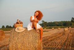 Mujer pelirroja que presenta en el campo cerca de una pila del heno Imagen de archivo libre de regalías