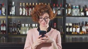 Mujer pelirroja que usa smartphone en la situación del restaurante cerca de soporte de la barra metrajes
