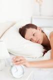 Mujer pelirroja soñolienta que apaga el reloj de alarma fotos de archivo