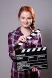 Mujer pelirroja sonriente hermosa que sostiene una chapaleta de la película Foto de archivo libre de regalías