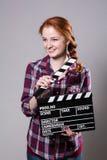 Mujer pelirroja sonriente hermosa que sostiene una chapaleta de la película Fotos de archivo libres de regalías