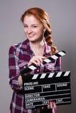 Mujer pelirroja sonriente hermosa que sostiene una chapaleta de la película Imagen de archivo