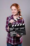 Mujer pelirroja sonriente hermosa que sostiene una chapaleta de la película Foto de archivo